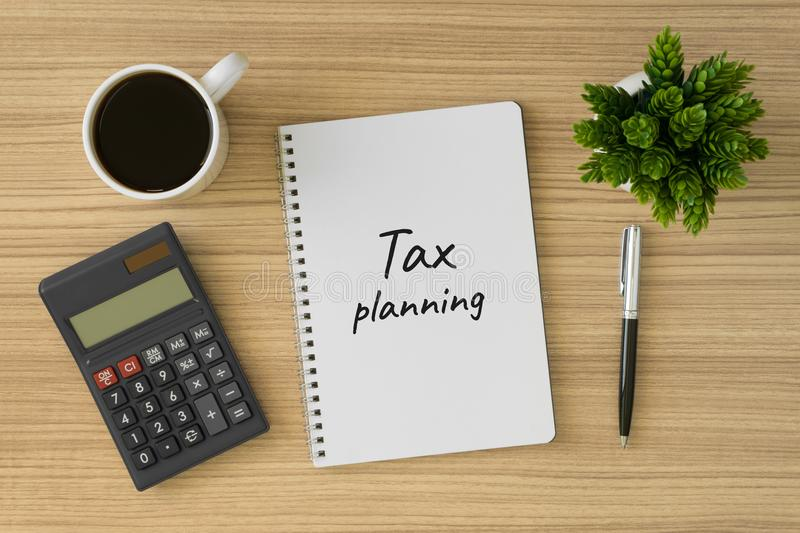 Tax planning written on notebook. Top view of wood desk with office supply royalty free stock image