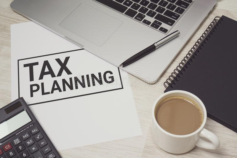 Tax Planning on white paper with laptop computer and coffee cup. Tax Planning written on white paper with laptop computer and coffee cup. Business and finance royalty free stock image