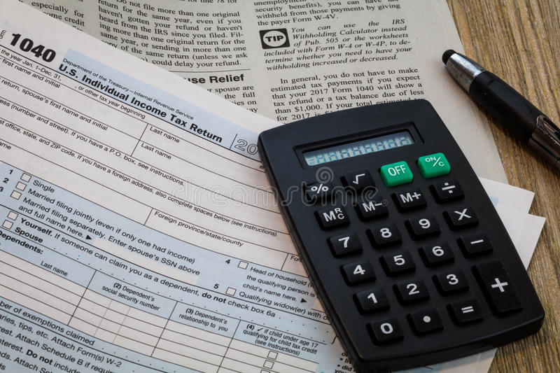 Tax preparation forms with pen and calculator, generic no year specified. Tax preparation forms and tax booklet US 1040 Tax form with pen and calculator stock photography