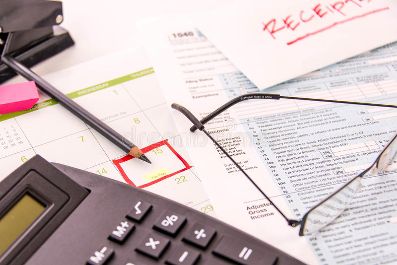 Tax preparation supplies, reading glasses and tax forms stock photos