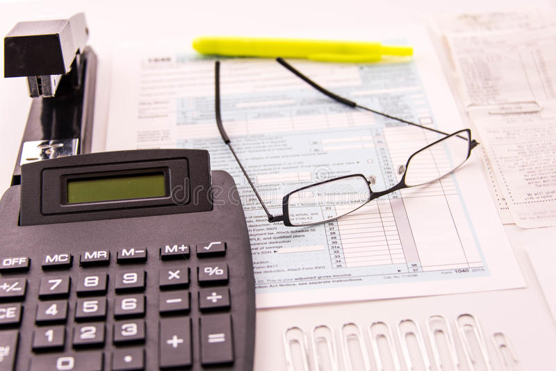 Tax preparation supplies, reading glasses and tax forms stock photography