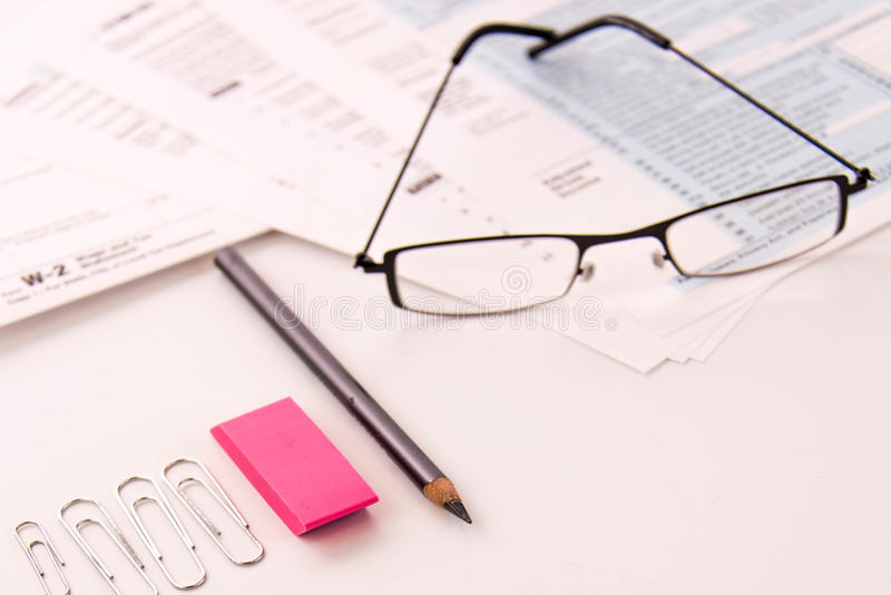 Tax preparation supplies, reading glasses and tax forms stock image
