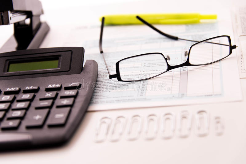 Tax preparation supplies, reading glasses and tax forms stock images