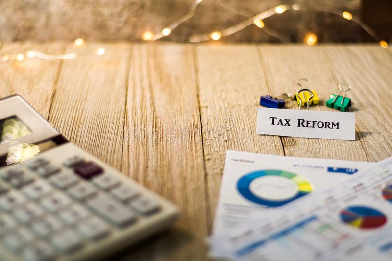 Tax Reform financial strategy motivational concept. Tax Reform motivational concept with charts and graphs on wooden board royalty free stock images