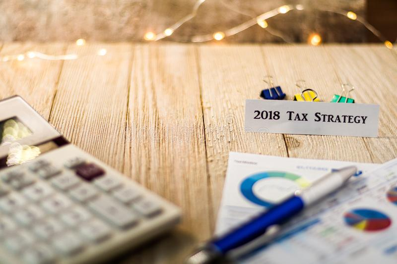 Tax Strategy for 2018 financial strategy motivational concept. Tax Reform motivational concept with charts and graphs on wooden board royalty free stock photo