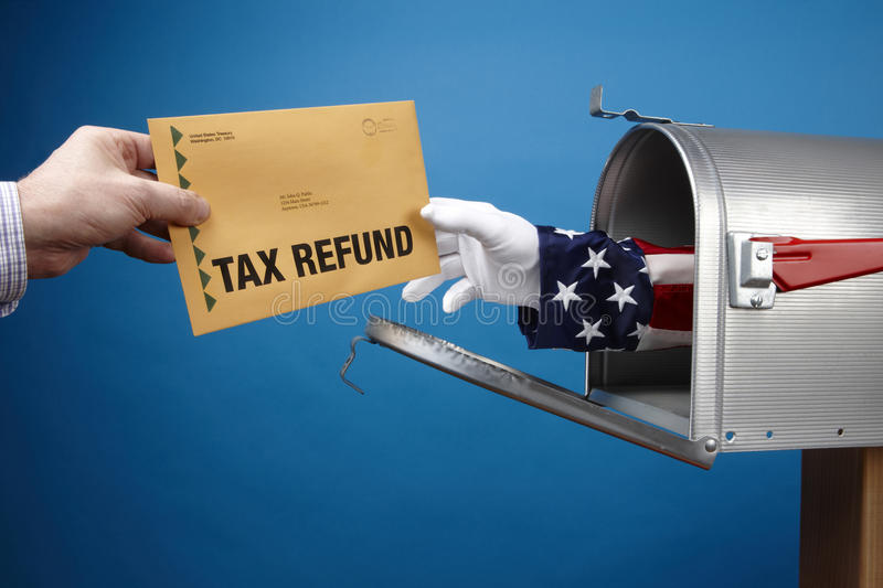 Tax Refund. Uncle Sam's arm comes through mailbox to give/take tax refund, includes copyspace stock photo