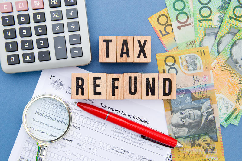 Tax Refund - Australia. Wooden letters with tax form, magnifying glass, money and calculator royalty free stock image
