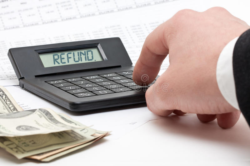 Tax refund calculation. Accountant doing taxes with calculator spelling REFUND - tax concept stock photos