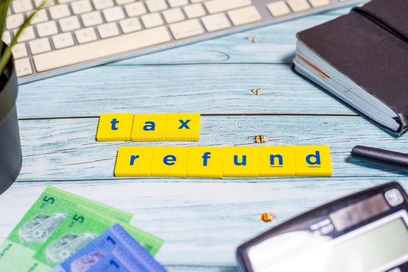 Tax Refund Concept - Calculator, keyboard, Ringgit Malaysia on blue wooden background.  royalty free stock photo