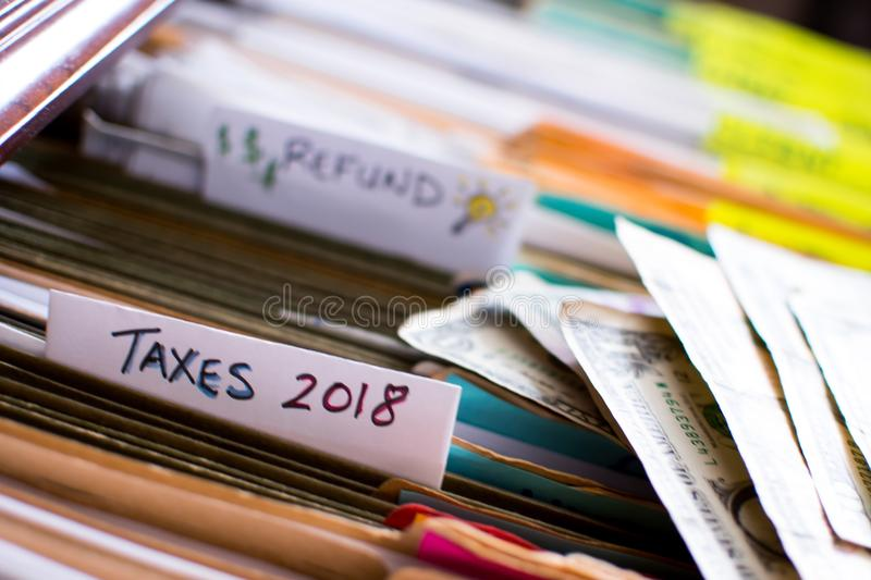 Tax refund and doing personal income taxes 2018. Taxes 2018 and words refund written on note cards with symbol for tax refund ideas and dollar signs credit and royalty free stock image