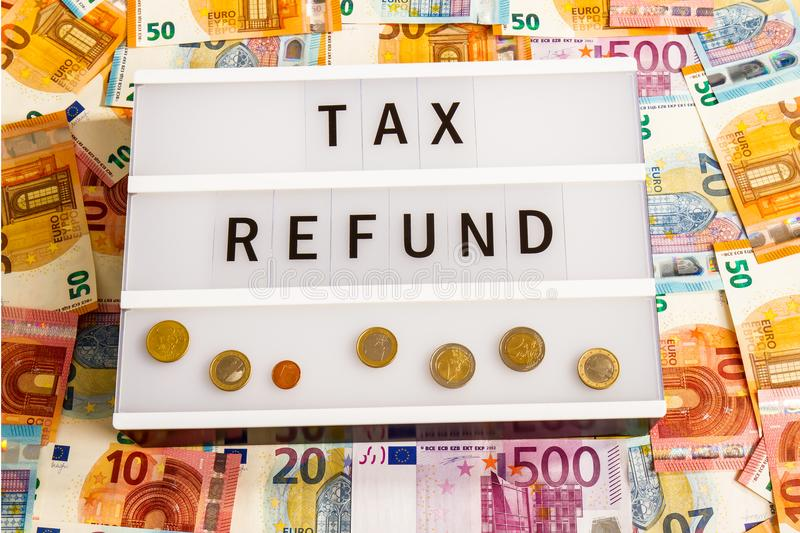 Tax Refund. Text Tax Refund written on lightbox surrounded with Euro Banknotes royalty free stock image