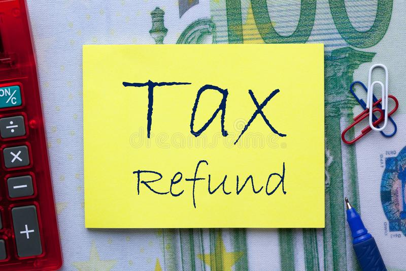Tax Refund Concept. Tax Refund written on note with pen a side and office supplies. Business concept royalty free stock photo