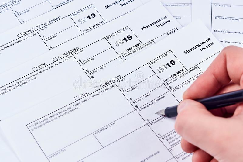 Human fills out the 1099-misc tax form. Tax reporting. Human fills out the 1099-misc tax form on background other forms royalty free stock images
