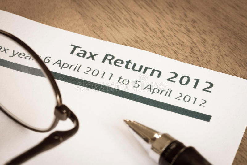 Tax return 2012. UK Income tax return form for 2012 on a desk with pen and spectacles stock images
