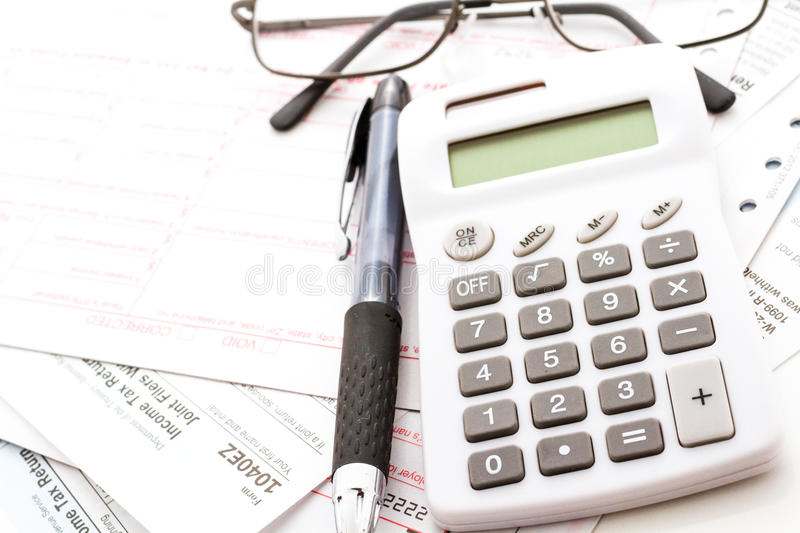 Tax return. Calculating numbers for income tax return with pen and calculato stock images