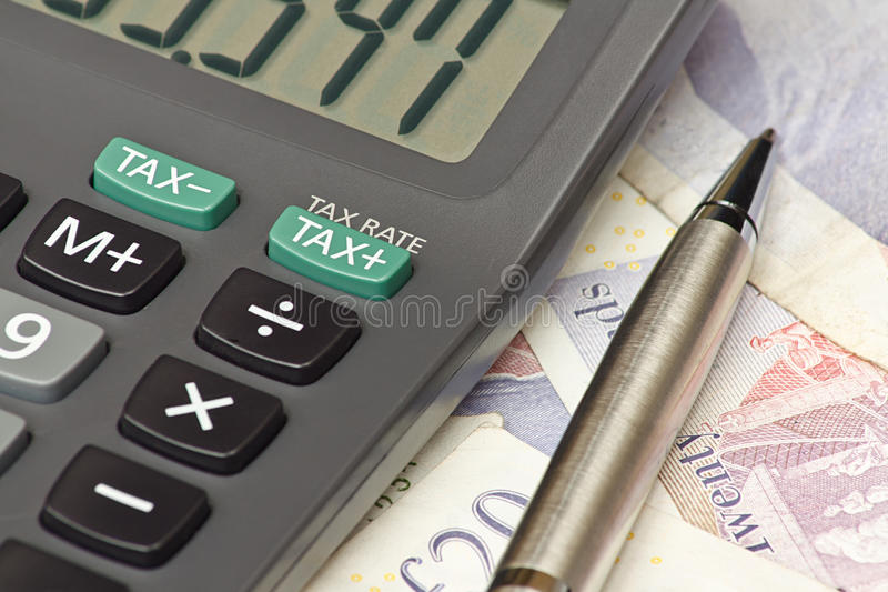 Tax return calculator. Calculator and pen symbolizing completing your personal Income tax returns for the inland revenue service or IRS stock images