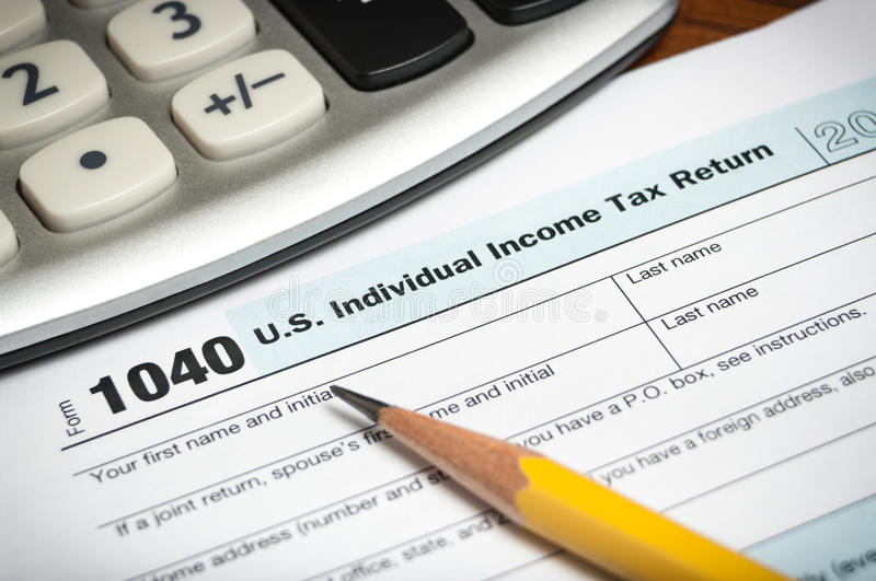 Tax return form. Close-up of a United States tax return form with a pencil and calculator royalty free stock photo