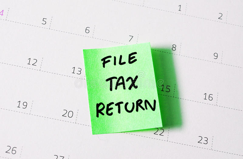 Tax return. Hand written reminder to file tax return on green note calendar background stock photography