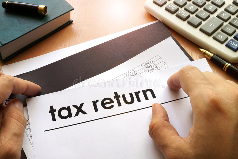 Tax return. Hands holding documents with title tax return stock photos