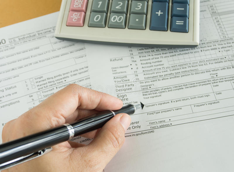 Tax return. Human hands will write in individual income tax return form stock image