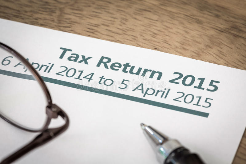 Tax return 2015. UK HMRC Income tax return form for 2015 on a desk with pen and glasses royalty free stock photos