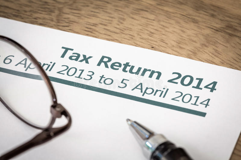 Tax return 2014. UK Income tax return form for 2014 on a desk with pen and glasses royalty free stock image