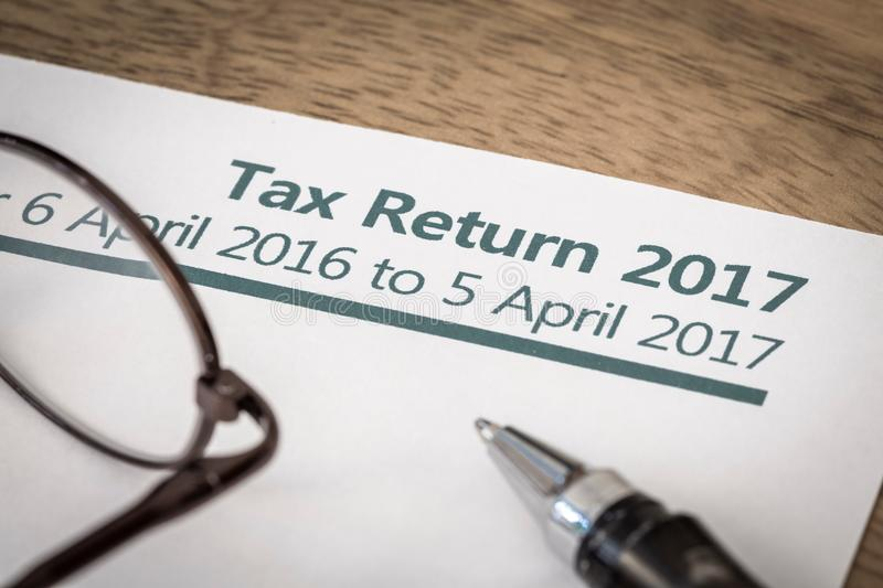 Tax return 2017. UK Income tax return form for 2017 on a desk with pen and glasses stock photos