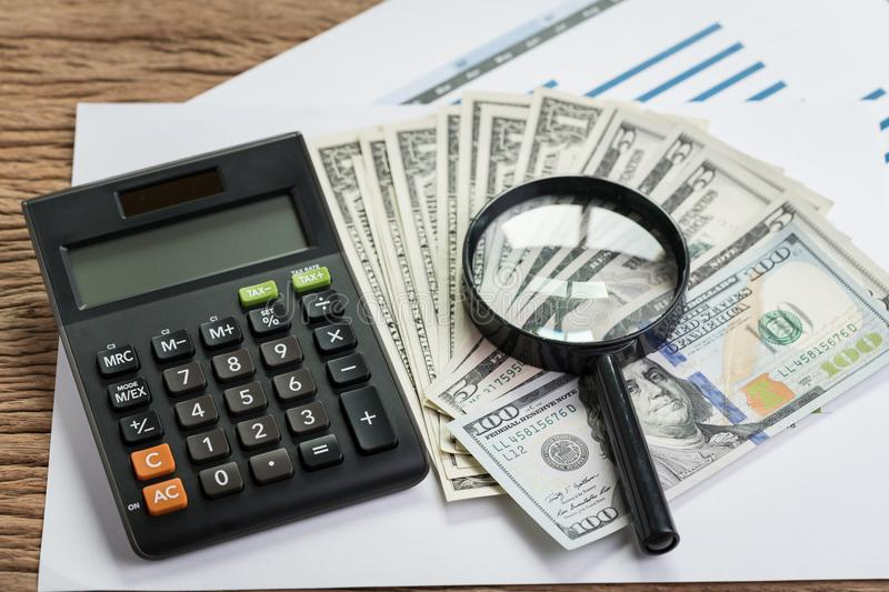 Tax, searching for yield or financial report review concept, mag. Nifier glass on pile of US Dollar banknotes with calculator on graph and chart performance stock image