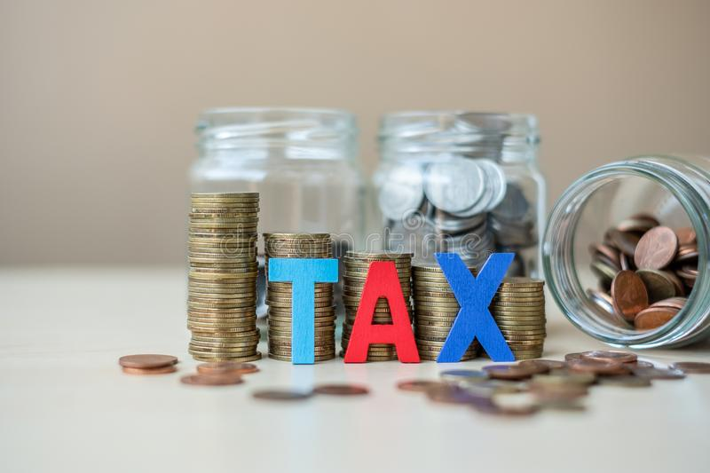 TAX text with golden coin growing money stairs or stack and glass jar on wooden table. business, investment, retirement planning,. Finance and Saving for the stock photography