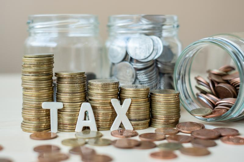 TAX text with golden coin growing money stairs or stack and glass jar on wooden table. business, investment, retirement planning,. Finance and Saving for the royalty free stock photo