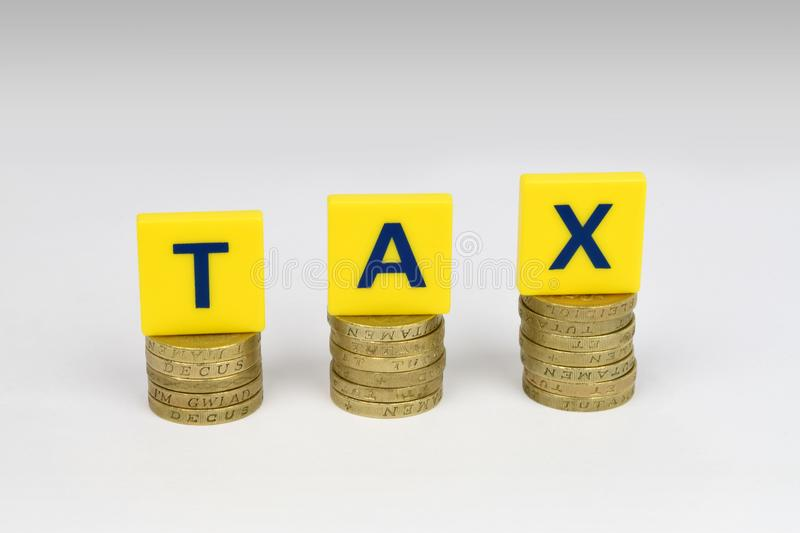Tax. Three piles of coins with letters spelling TAX on top of them. A financial metaphor on the increasing burden of tax royalty free stock photos