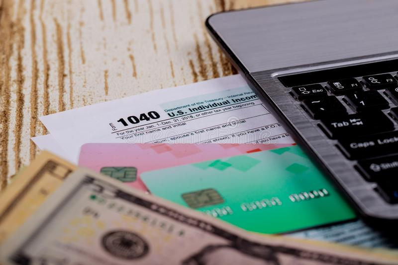 Tax time Closeup of U.S. 1040 tax return with U S dollars bills and for April Calendar. Tax time - Closeup of U.S. 1040 tax return with U S dollars bills pay tax royalty free stock image