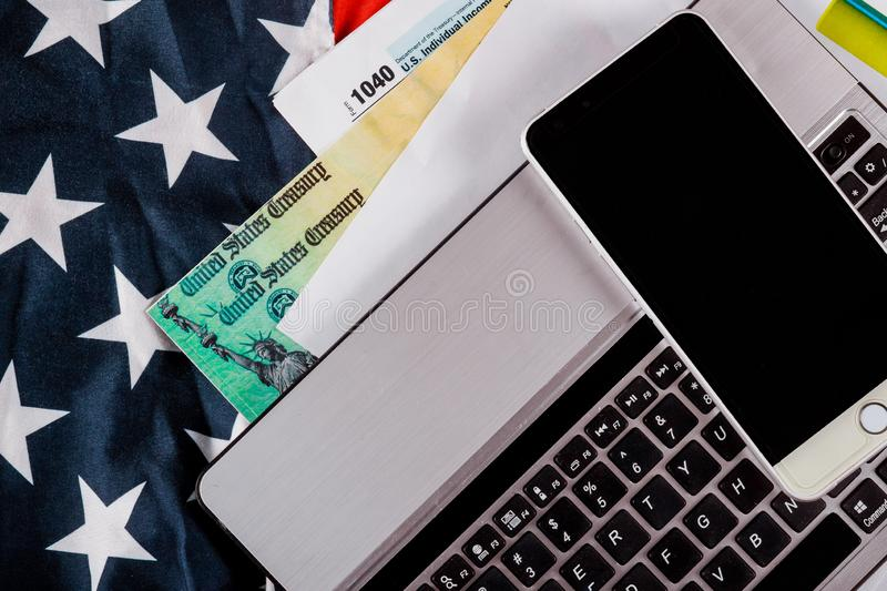 Tax time Closeup of U.S. 1040 tax return with US flag and for April. Tax time Closeup of U.S. 1040 tax return with US flag pay tax for April and refund check royalty free stock images