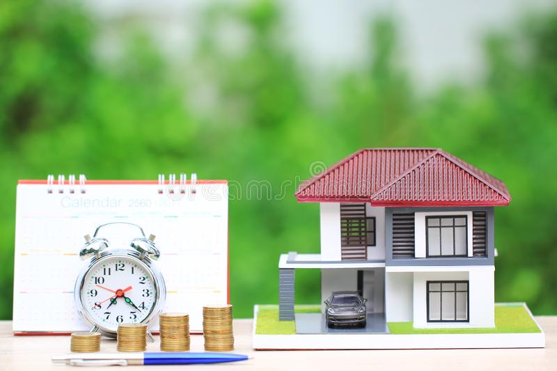 Tax time concept, Model house and car with stacking coins money and alarm clock and calendar on natural green background royalty free stock image