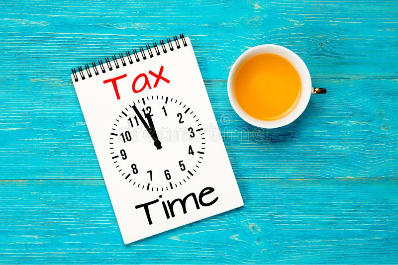 Tax time, message with clock in notepad over turquoise table royalty free stock images