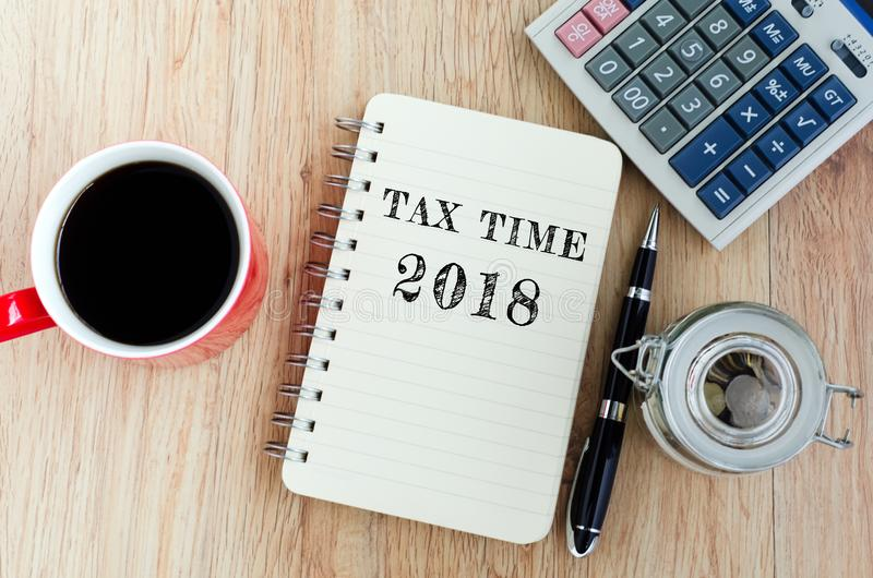 Tax Time text on notepad. Coffee, jar coins, pen and calculator on top of wooden table royalty free stock photo