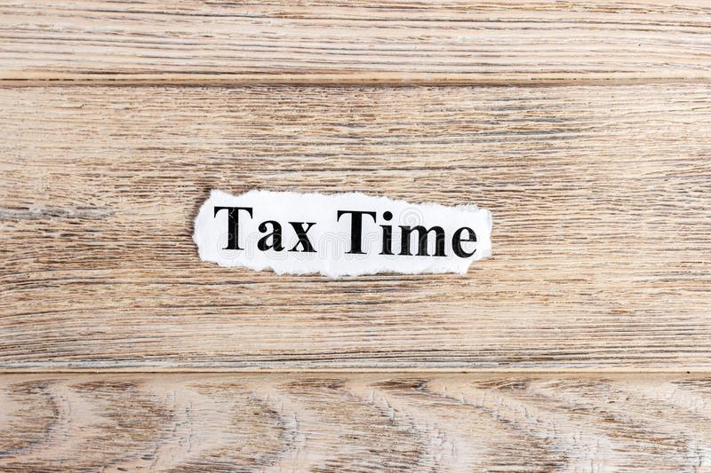 Tax Time text on paper. Word Tax Time on torn paper. Concept Image.  stock photography
