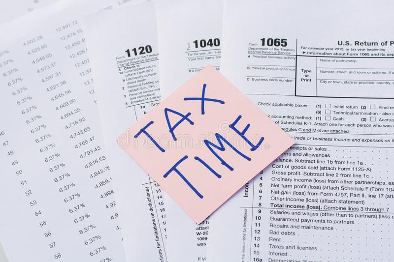 Tax Time written on pink sticker note with on U.S. tax form.  royalty free stock photography