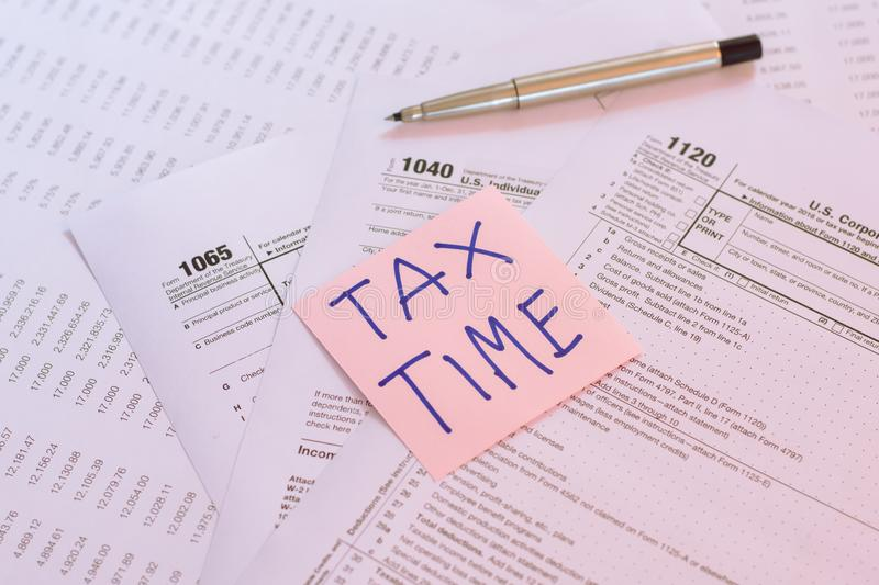 Tax Time written on pink sticker note with on U.S. tax form.  stock photo