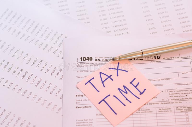 Tax Time written on pink sticker note with on U.S. tax form.  stock photos