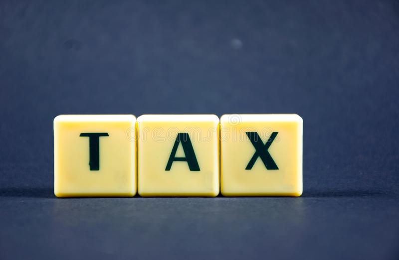 Tax word concept Dark background image using by block letter royalty free stock photos