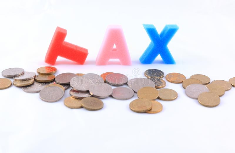 Tax. Word spelled out with gold and silver coins in foreground. Isolated on a white background royalty free stock photos
