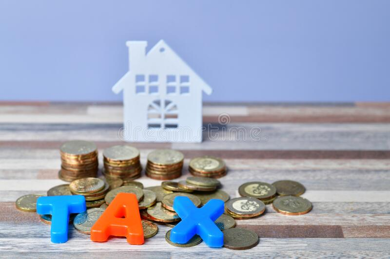 TAX word on wooden home and stack money coins concept stock image