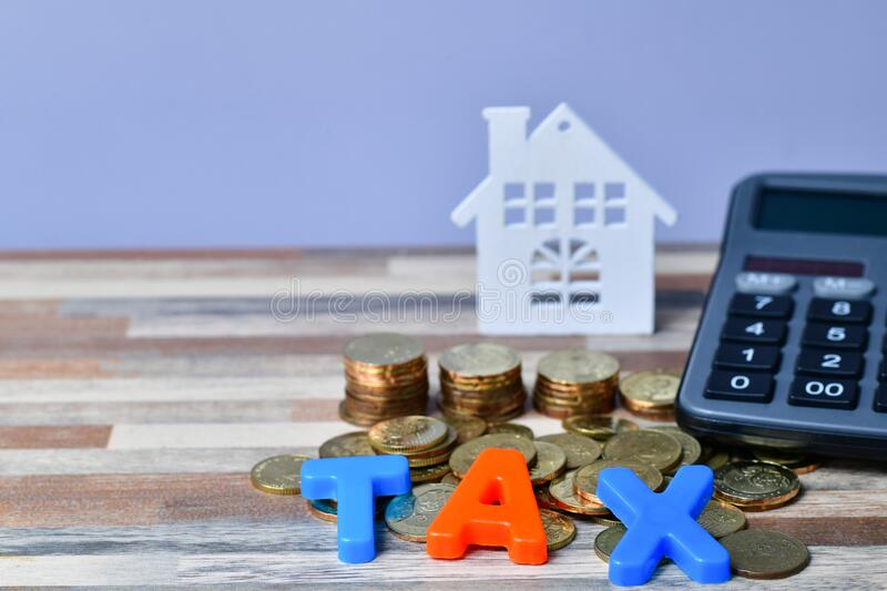 TAX word on wooden home and stack money coins concept stock photo