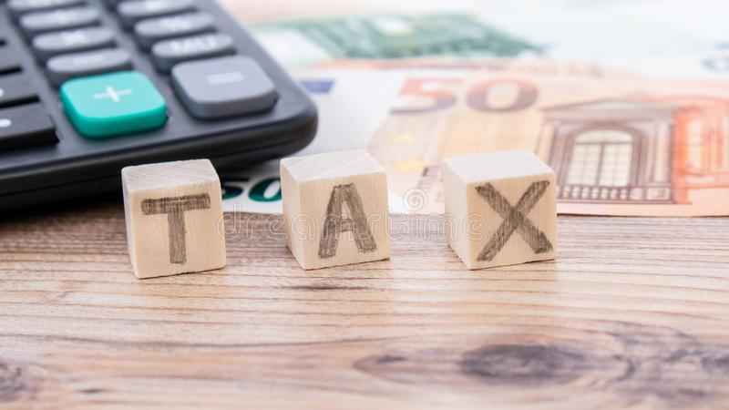 Tax word writen on wooden cubes. Euro banknotes Laid out in a semicicircle and calculator. Money finance earning sector concept. C. Opy space for text. Taxes and stock images