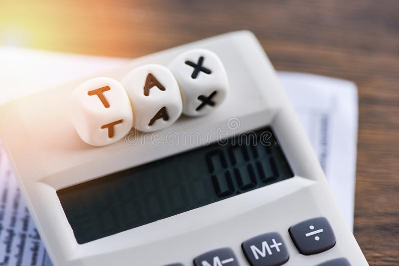 Tax words on calculator on invoice bill paper finances for time tax calculation royalty free stock images