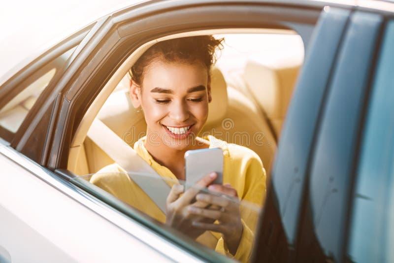 taxa Afrikansk kvinna som anv?nder telefonen p? baks?tet arkivfoton