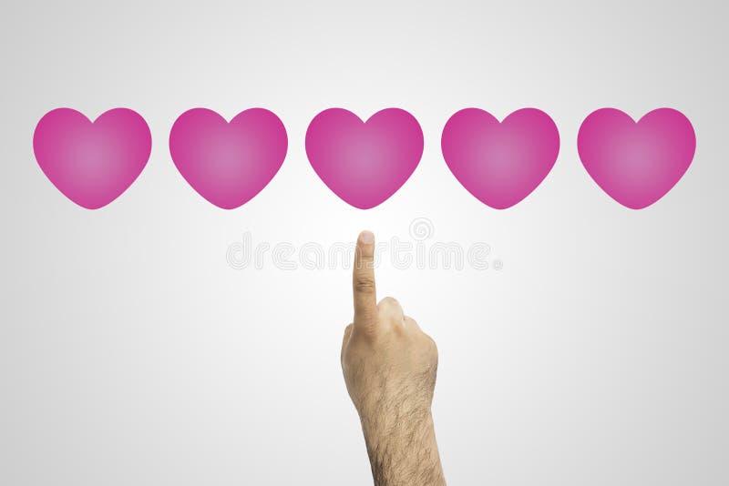 taxa avaliação vermelha de 5 corações A mão clica sobre uma avaliação vermelha de cinco corações Mão do homem de negócios que dá  imagens de stock royalty free