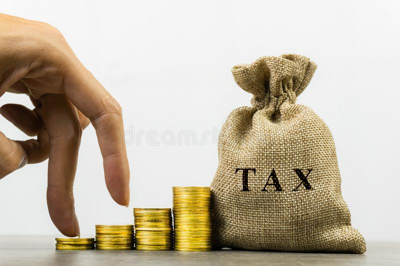 Taxation and Annual tax concept. A man hand on rising stack of coins and tax bag on white background. Depicts a income planning, stock images