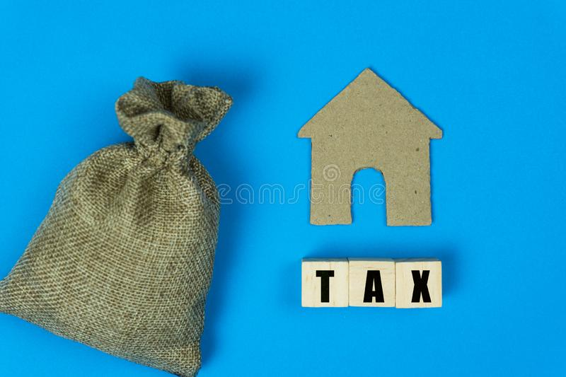 Taxation and Annual tax concept. A message on wooden block with a small house paper cut and money bag  on blue background.  royalty free stock images